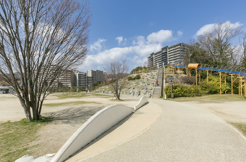 現況写真 彩都西公園まで徒歩7分(約540m)。敷地面積約52000平方メートルの広大な公園。芝生広場、全長70mのローラー滑り台や大きなバッタの形をした滑り台などユニークな遊具があります。