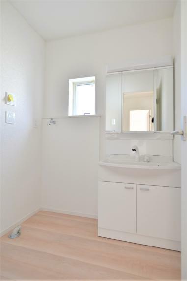 洗面化粧台 〈13号棟写真〉 お手入れしやすいシャワー機能付洗面化粧台。大きな鏡で朝の準備もスムーズにできます。