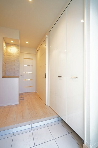 玄関 No.7_玄関ホール(撮影_2021年8月)家族を出迎える玄関ホール。清潔感と高級感を演出する為、白を基調としたタイルに。美しい木目の際立つフローリングが特徴的。