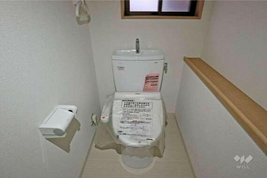 トイレ 1階トイレ。温水洗浄便座つきで、向かって右手には携帯などを一時置いておける台を設置。