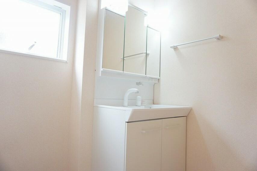 洗面化粧台 同仕様写真。シャワーホース付のシャンプードレッサー。三面鏡付きで毎朝の支度もはかどります。歯みがきセットや化粧品もきれいに整頓できますよ。
