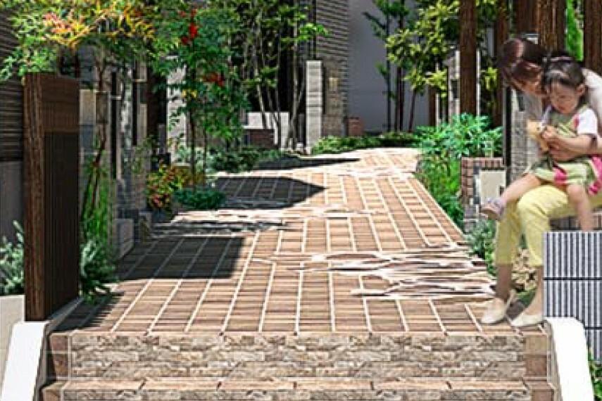 現況外観写真 【インターロッキング】  歩行者専用のフットパスに施した石畳風のインターロッキングは、植栽の緑や木目調の外壁と美しく調和。吸水性に優れ、雨の日の安全な歩行にも配慮しています。