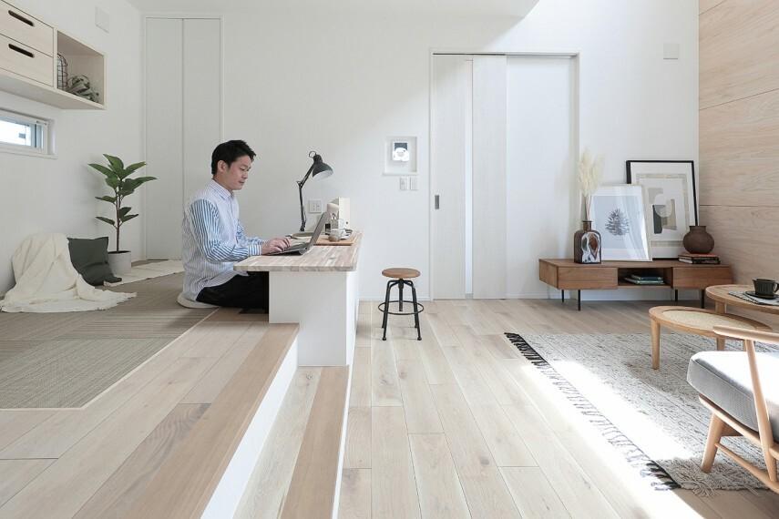 居間・リビング 【ステージリビング】  リビングの一角に小上がりのステージを設け、リビング側に向けて掘り机を設置。リビング全体が見渡せ、家族と適度な距離を保ちながら仕事や勉強ができます。※号棟により採用状況が異なります。