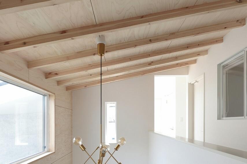 居間・リビング 【国産檜合板と化粧梁】  国産材を有効活用した檜合板を、リビングの壁と天井、玄関ホールの天井に採用しました。リビングの天井には、アクセントとして木の風合いを持つ化粧梁をデザイン。自然の安らぎで空間を満たします。