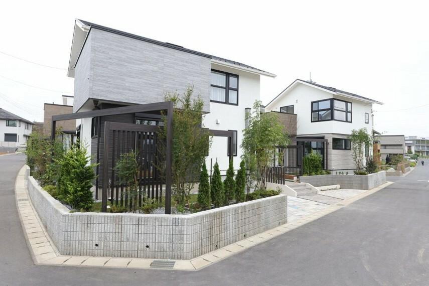 現況外観写真 【緑の風景と調和するモダンな邸宅】  邸宅風のスタンダードな切妻屋根や寄棟屋根でありながら、都市邸宅としてのモダンなフォルムをデザイン。環境にも家族にも優しい省エネ性能「認定低酸素住宅」です。