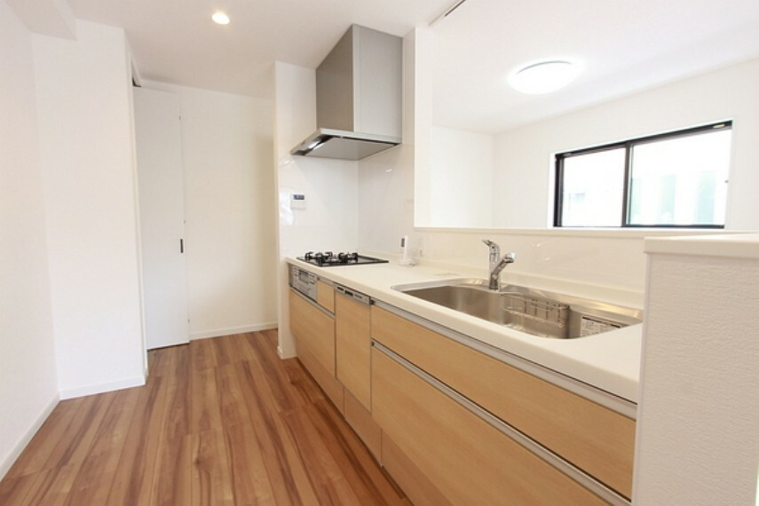 キッチン 家族との会話もしやすい開放的なキッチン コンロ回りに壁と換気扇があり、油や匂いが広がるのを抑えられます 両側から出入り可能 パントリーとして使える収納もあり便利です