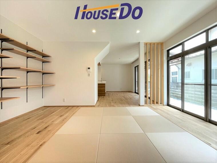 居間・リビング 大きな窓があることによって、外との一体感が生まれ、空間をより広く見せる役目を果たしているとともに、窓から見える緑や、外の景色もデザインに取り込まれているかのようです。