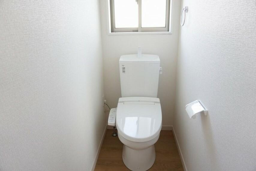 トイレ 同仕様写真。バリアフリーに配慮して便座から立ち上がりやすくする手すり、また棚やタオル掛けも設けています。