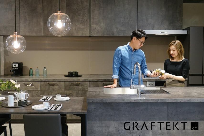 【GRAFTECTキッチン】  家具のようなキッチンでLDKをコーディネートするGRAFTECTキッチン。キッチンをを引き立てるモダンスクェアデザインの手づくり板金シンクは、天板とシームレスに仕上げ、お手入れしやすく、いつまでも清潔に使えます。キズ、摩擦、汚れ、水、衝撃に強い高機能メラニン素材「エバルト」を天板部分に採用しています。※号棟により採用状況が異なります。
