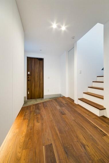 外観・現況 【施工例】 玄関ドアは床と色味をあわせてやさしい木目調のドアを選択。カラーに統一感を持たせたナチュラルで温かみのある玄関。 収納の下に設けた足元を照らす間接照明が落ち着きと高級感を演出します。