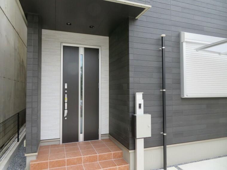 玄関 ドア正面に窓を配し、壁面下部までタイルを貼るなど変化をつけた玄関。