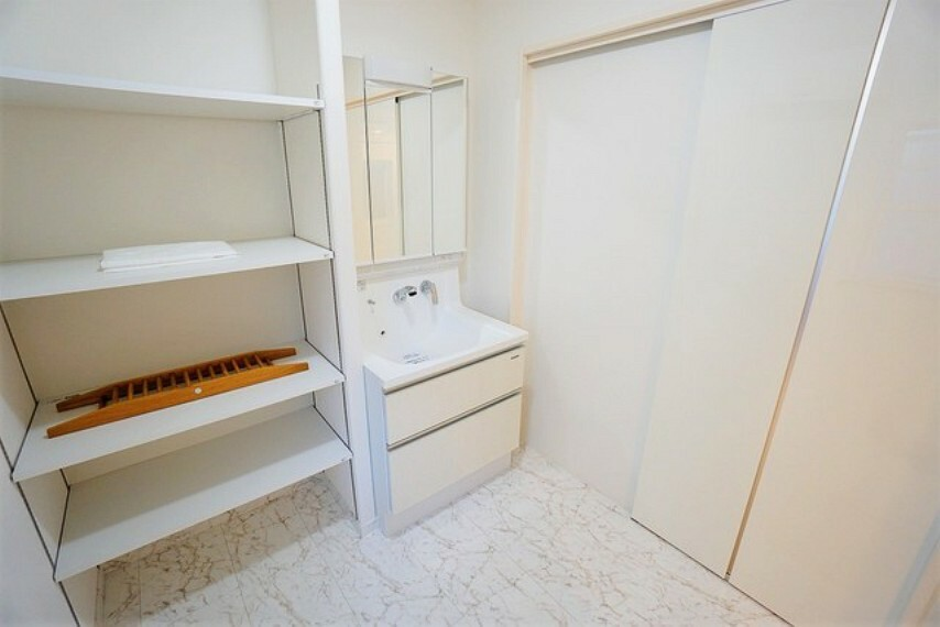 洗面化粧台 便利な洗面室収納。散らかりがちなバスタオルや清掃用品、化粧品や予備のシャンプー等もきれいに整頓できますね。落ち着いたホワイトトーンの扉なので、観葉植物を置いてもおしゃれですね。