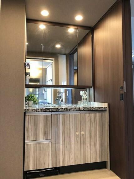 洗面化粧台 洗面化粧台カウンターは高級感のある天然御影石を採用。三面鏡の裏は全て収納の為にスッキリと水回りを利用する事が可能です。三面鏡の下部にも証明を設置しております。