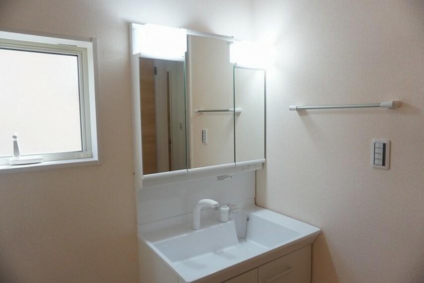 洗面化粧台 (同仕様写真)。三面鏡つき洗面台。収納も一体型になっているので、ドライヤーやヘアアイロンの置き場に困りませんね。