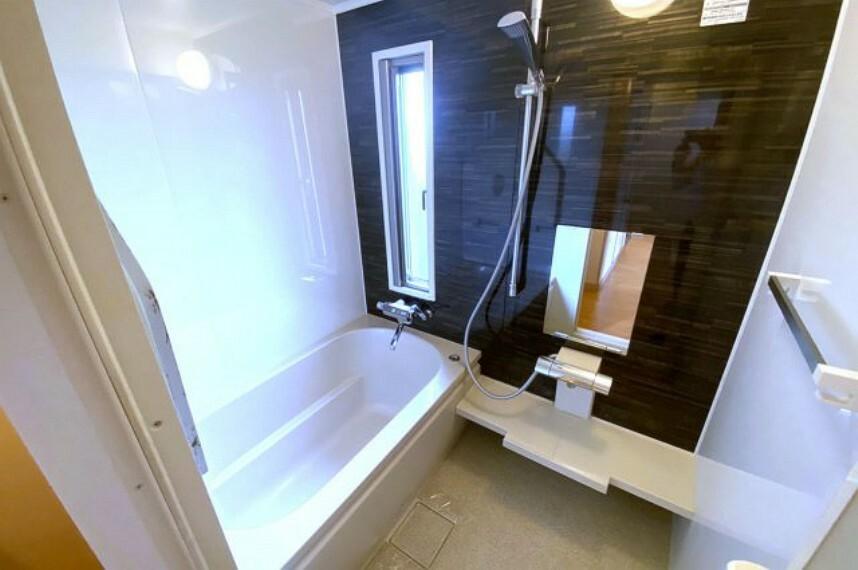 浴室 黒い壁がシックなシステムバスです。窓付きで、換気がしやすい浴室です。
