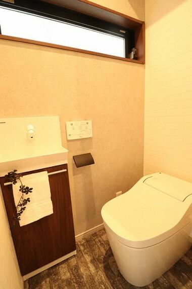 【施工写真/トイレ】 温水洗浄便座付きのトイレです。背面上部に棚を設け、トイレットペーパーなどの物置や飾り棚としての利用が可能です。