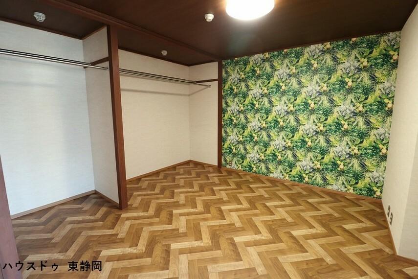 居間・リビング ボタニカル調の印象的なクロスを使用し、リラックスできる空間です。リノベーションした収納は、衣服用のポール付きで使い勝手が良いですね。